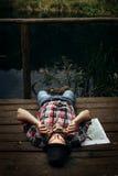 Modieuze hipsterreiziger het spelen harmonika bij zonnig meer in stock foto