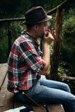 Modieuze hipsterreiziger het spelen harmonika bij zonnig meer in stock afbeelding