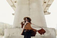 Modieuze hipstervrouw die pret, in hoed met winderig haar hebben dichtbij ri Royalty-vrije Stock Foto