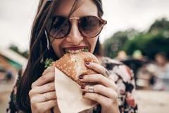 modieuze hipstervrouw die sappige hamburger en het eten houden Bohomeisje royalty-vrije stock fotografie