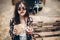 modieuze hipstervrouw die sappige hamburger en limonade houden bohogi stock afbeeldingen