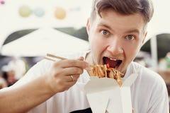 Modieuze hongerige mens die heerlijke woknoedels met grappige emoties van kartondoos eten met bamboeeetstokjes Het Aziatische voe royalty-vrije stock afbeelding