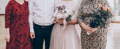Modieuze huwelijksbruid met boeket en bruidegom die foto met F nemen stock afbeeldingen