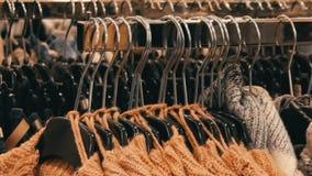 Modieuze inzameling van warme kleren Groot aantal nieuwe warme modieuze sweaters die van verschillende kleuren op hangers hangen stock videobeelden