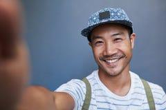 Modieuze jonge Aziatische mens die een selfie buiten nemen stock afbeelding