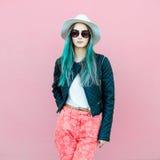 Modieuze jonge bloggervrouw met blauw haar die toevallige stijluitrusting met zwart jasje, witte hoed, roze jeans en zonnebril dr Stock Foto