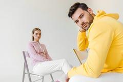 modieuze jonge mannelijke en vrouwelijke modellen in roze en gele hoodies die op stoelen zitten royalty-vrije stock afbeelding