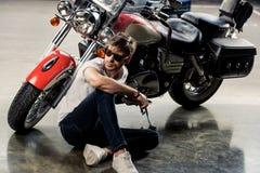 Modieuze jonge mens in dichtbij motorfiets zitten en zonnebril die weg eruit zien stock foto