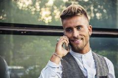 Modieuze jonge mens die bij telefoon de openlucht status spreken royalty-vrije stock foto's