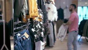 Modieuze Jonge Mens die Doeken in Opslag kiezen Mannelijke Klant bij het Winkelen stock footage