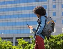 Modieuze jonge mens die met mobiele telefoon lopen Royalty-vrije Stock Afbeelding