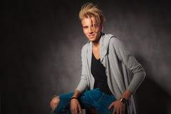 Modieuze jonge mens die ruwe jeans dragen die in studiorug stellen Stock Afbeeldingen
