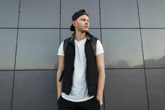 Modieuze jonge mens in een zwart GLB en een zwart modieus vest stock foto's
