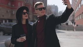 Modieuze jonge paartoeristen die selfie in stadsstraat maken stock footage