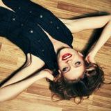Modieuze jonge vrouw die bij houten vloer en het lachen liggen stock afbeelding
