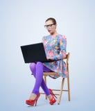 Modieuze jonge vrouw die in glazen op een stoel met laptop zitten Royalty-vrije Stock Foto
