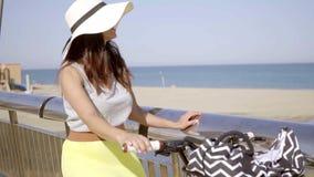 Modieuze jonge vrouw die haar fiets berijden bij de kust stock videobeelden