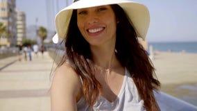 Modieuze jonge vrouw die haar fiets berijden bij de kust stock footage