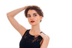 Modieuze jonge vrouw die met die rode lippen in zwarte kleding weg kijken op witte achtergrond wordt geïsoleerd Royalty-vrije Stock Foto