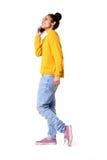 Modieuze jonge vrouw die op mobiele telefoon spreken Stock Afbeeldingen