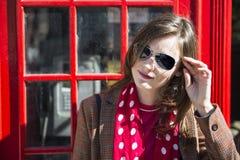 Modieuze jonge vrouw die op rode telefooncel leunt Stock Fotografie