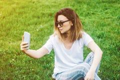 Modieuze jonge vrouw die selfie in het park met een smartphone maken royalty-vrije stock fotografie
