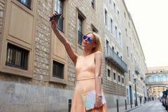 Modieuze jonge vrouw die zelfportret met slimme telefoon nemen Stock Afbeeldingen