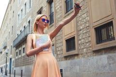 Modieuze jonge vrouw die zelfportret met slimme telefoon nemen, voelend goed en gelukkig in reis Royalty-vrije Stock Foto