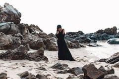 Modieuze jonge vrouw in elegante zwarte kleding op het steenstrand royalty-vrije stock afbeeldingen