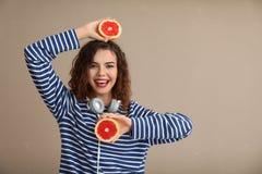 Modieuze jonge vrouw met de helften van grapefruit op kleurenachtergrond royalty-vrije stock fotografie