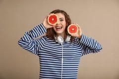 Modieuze jonge vrouw met de helften van grapefruit op kleurenachtergrond royalty-vrije stock afbeeldingen