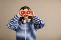 Modieuze jonge vrouw met de helften van grapefruit op kleurenachtergrond stock foto