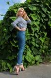 Modieuze jonge vrouw met krullend haar die gestreepte blouse en j dragen Stock Afbeelding