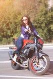 Modieuze jonge vrouw met zonnebril, lilac korte windjekker en jeans met een mooi lichaam op een rode sportenfiets royalty-vrije stock foto's