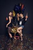 Modieuze jonge vrouwen die met flessen van alcoholdranken en glanzende ballons stellen royalty-vrije stock afbeeldingen