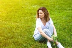 Modieuze jonge vrouwenzitting op groen gras in zonnige warme dag stock afbeelding