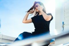 Modieuze jonge vrouwenzitting in openlucht op balkon en het spreken door mobiele telefoon royalty-vrije stock fotografie