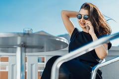 Modieuze jonge vrouwenzitting in openlucht op balkon en het spreken door mobiele telefoon stock fotografie