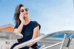 Modieuze jonge vrouwenzitting in openlucht op balkon en het spreken door mobiele telefoon stock foto's