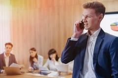 Modieuze jonge zakenman die een jasje en een overhemd op de achtergrond van een werkend bureau met mensen dragen die op een mobie royalty-vrije stock fotografie