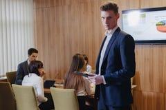Modieuze jonge zakenman die een jasje en een overhemd op de achtergrond van een werkend bureau met mensen dragen die met een tabl royalty-vrije stock fotografie