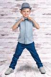 Modieuze jongen in elegante kostuum en hoed Een kleine zakenman Kinderen` s manier Royalty-vrije Stock Foto