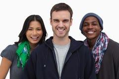 Modieuze jongeren die bij camera glimlachen Stock Afbeeldingen