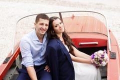 Modieuze jonggehuwden die in een boot op het strand zitten. Stock Fotografie