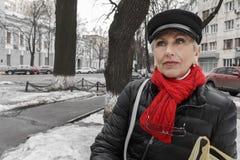 Modieuze kalme vrouw op middelbare leeftijd in rode sjaal royalty-vrije stock fotografie