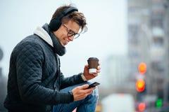 Modieuze kerel in hoofdtelefoon die zijn mobiele telefoon in openlucht met behulp van stock afbeelding