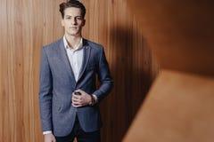 Modieuze kerel in jasje op kantoor op eenvoudige houten achtergrond royalty-vrije stock fotografie