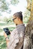 Modieuze kerel met tablet in de zomerpark royalty-vrije stock fotografie