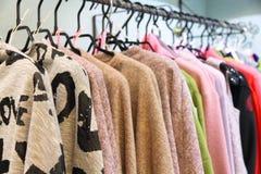 Modieuze kleren op hangers in een opslag Stock Afbeelding