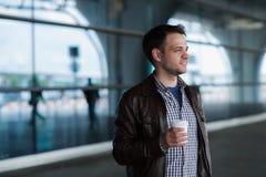 Modieuze knappe jonge mannelijke reiziger met varkenshaar die zich in openlucht dichtbij de luchthaventerminal bevinden Mens die  stock fotografie